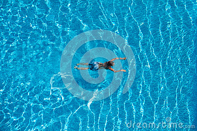 Boy is swimming in a swimming pool. Top view.