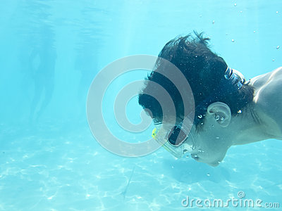 Boy swimming underwater in ocean