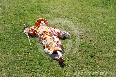 Boy with sword lying on the grass