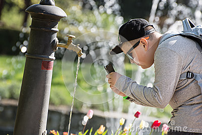 Boy taking photo - drinking water flowing from the faucet