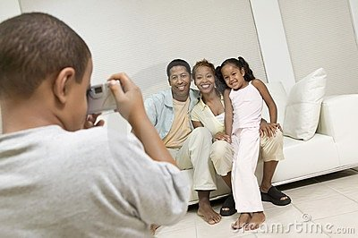 Boy Taking Picture of Family on sofa