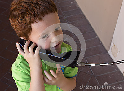 Boy talking on public telephone