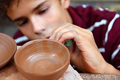 Boy teen potter clay bowl working