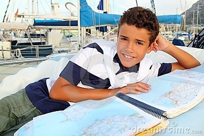 Boy teen sailor lying on marina boat chart map