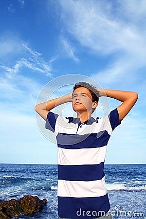 Boy teenager hands in head relaxed in blue ocean