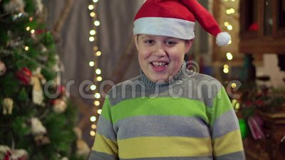 5ea4d1a76493f A Boy Teenager In A Hat Santa Claus Is Dancing Near The Christmas Tree. Christmas  Holiday