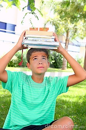 Boy teenager student holding head stacked books