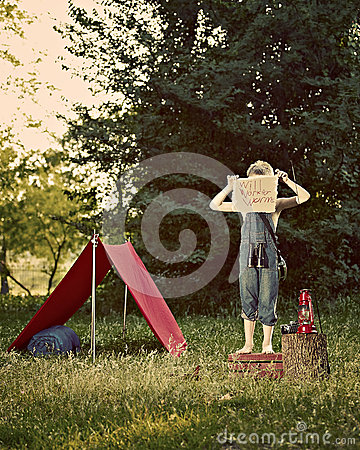 Boy with tent in meadow