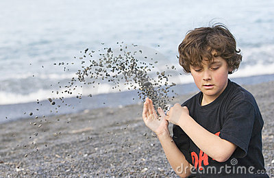 Boy throwing shingle on beach