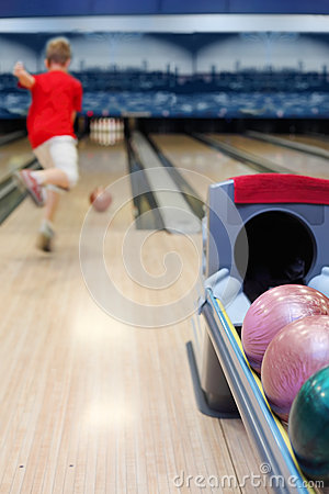 Boy throws ball in bowling