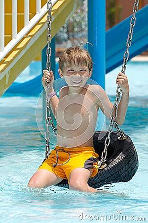Boy on tire swing in pool