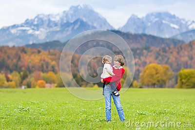Boy with toddler sister in field in mountainsa