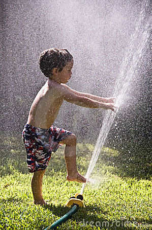 Boy toes fingers in sprinkler