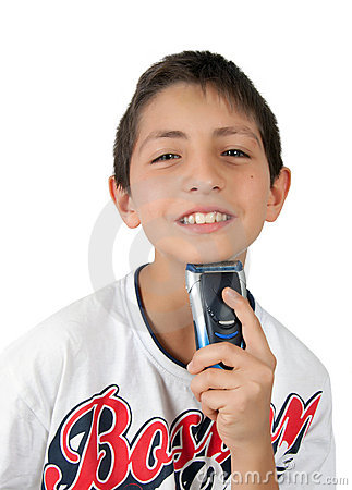 Boy toothy smiles and shaving chin with shaver