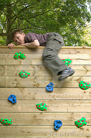 Boy on top of a climbing wall