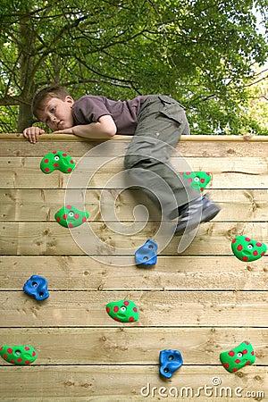 Boy on top of a climbing wall