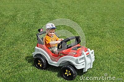Boy in toy car on grass