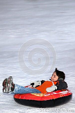 Boy Tubing Down Snowy Hill.