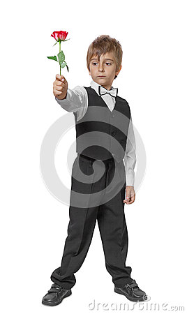 Boy in a tuxedo with a rose in hand.