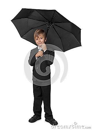 Boy in a tuxedo, under an umbrella.