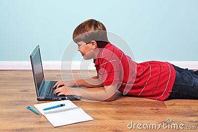 Boy typing on his laptop