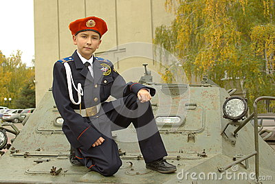 Boy in uniform with an armored troop carrier