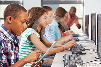 Boy Using Digital Tablet In Computer Class