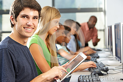 Boy Using Digital Tablet In Computer Class