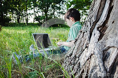 Boy using his laptop outdoor in park on grass