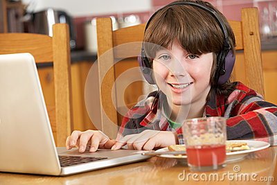 Boy Using Laptop Whilst Eating Breakfast