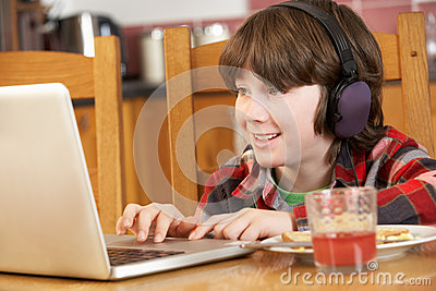 Boy Using Laptop Whilst Eating Breakfast
