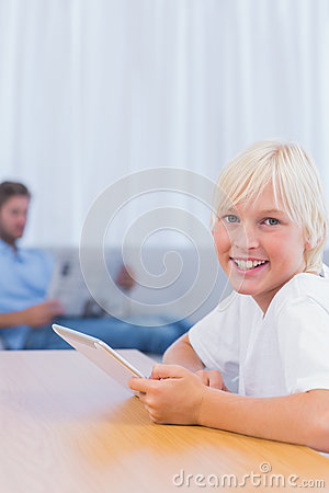 Boy using tablet with his father reading a book on the couch
