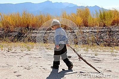 Boy walking along river
