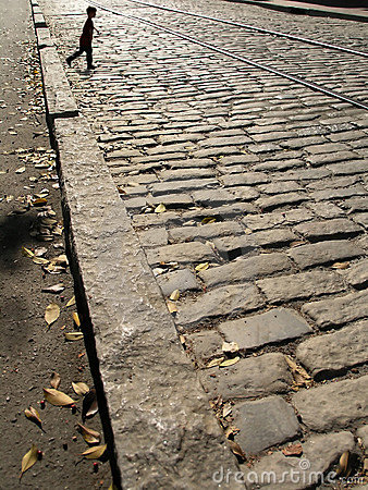 Boy walking cobblestones