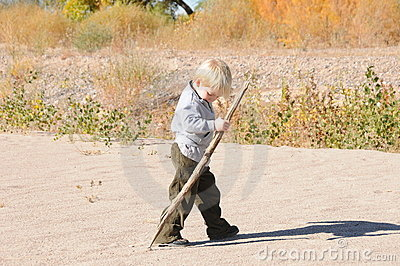 Boy walking on sand with stick