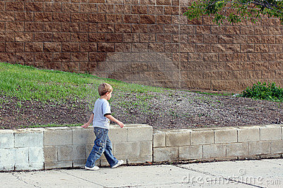 Boy walking on sidewalk