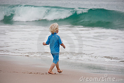 Boy walking towards waves