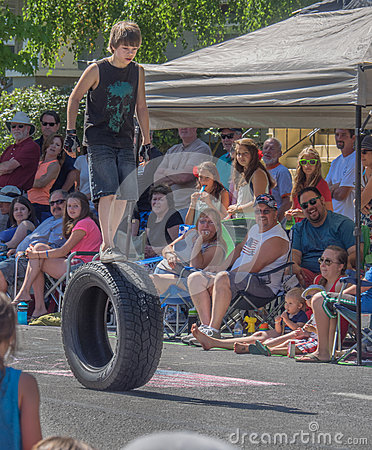 Free Boy Walks On Rolling Tire In Parade Stock Photography - 86556422