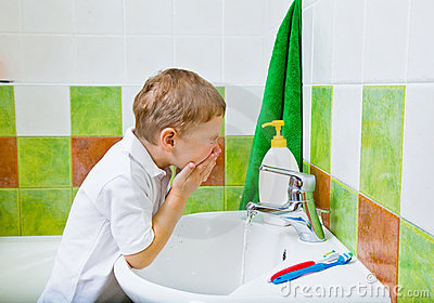 Boy washes the face