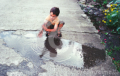 Boy washing hands in puddle