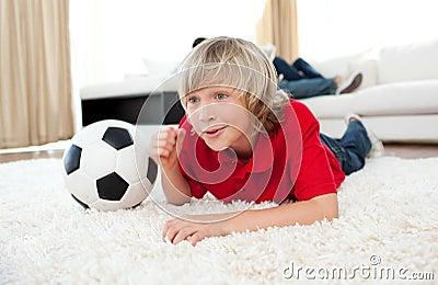 Boy watching football match lying on the floor