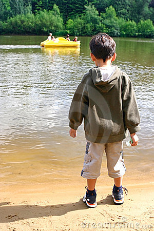 Boy watching pedalo in lake