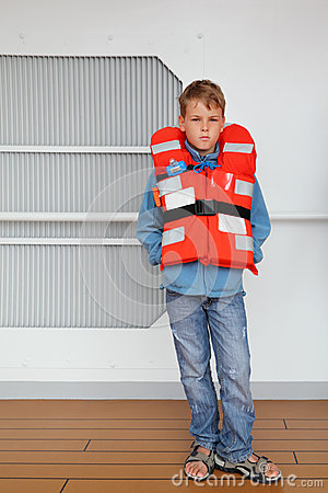 Boy wearing in life jacket stands at deck of ship