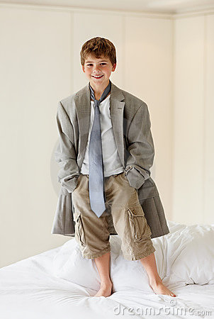 Boy wearing an oversized coat standing on bed