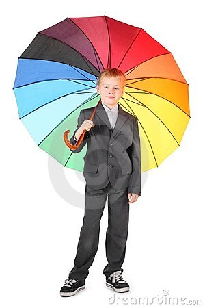 Boy wearing suit is standing with umbrella