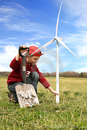 Boy with windmills and spade on the field