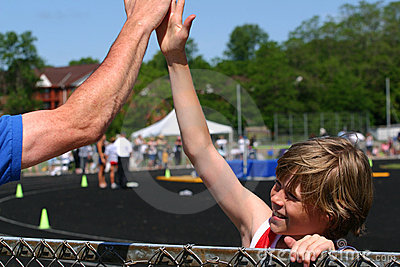 Boy wins race, congratulated by coach