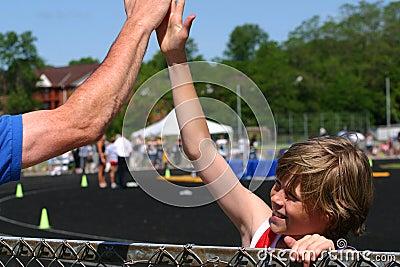 Boy wins race, congratulated by coach