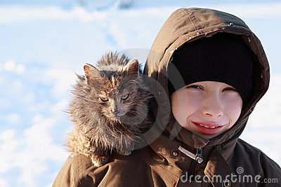 Boy at winter outdoors, cat sits on shoulder