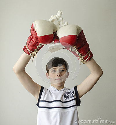 Free Boy With His Hands Raised In Boxing Gloves In A Victory Gesture With A Figurine Of A Boxer Royalty Free Stock Photos - 85615758